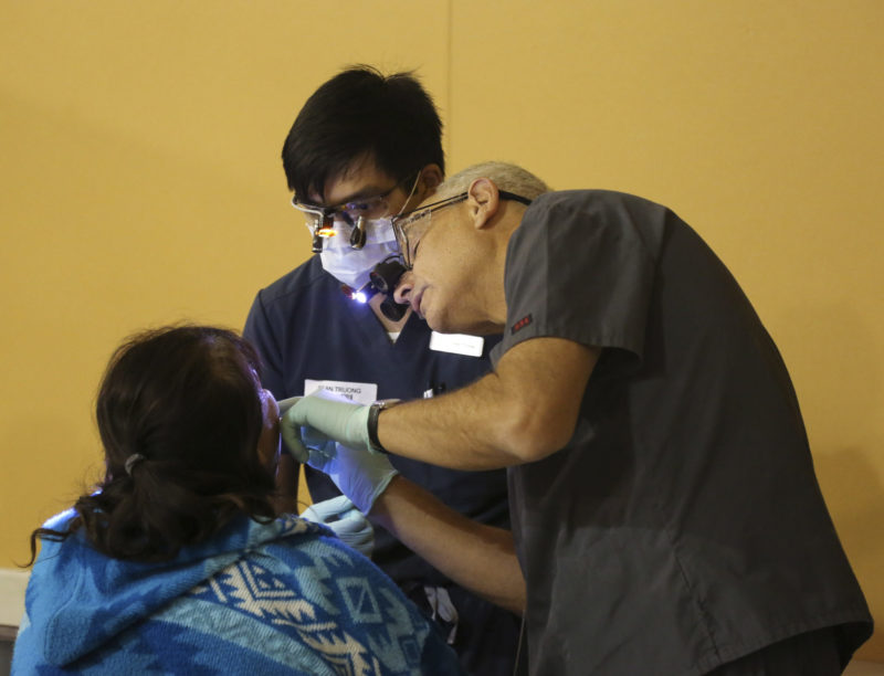 UNLV Professor Dr. Jay Morgenstern examines a patient at the RAM clinic while a UNLV dentistry student observes.