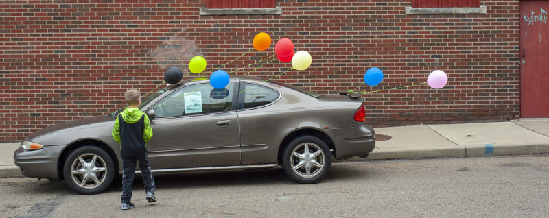 Child in front of a car with balloons