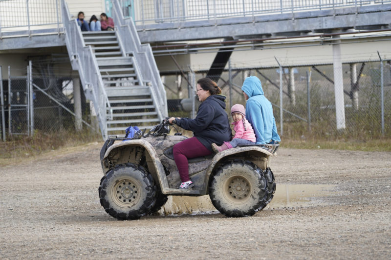 Mother and daughter riding four-wheeler.